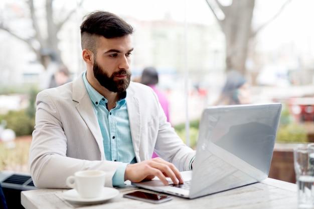 L'uomo barbuto bello in vestito bianco e blu alla moda lavora al computer che controlla i email.