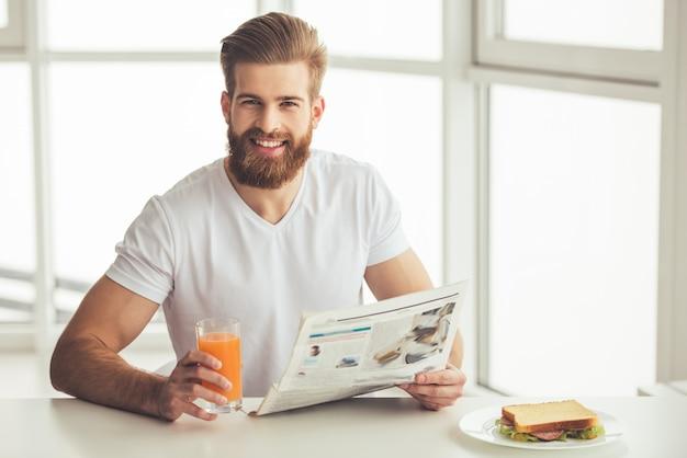 L'uomo barbuto bello sta leggendo un giornale
