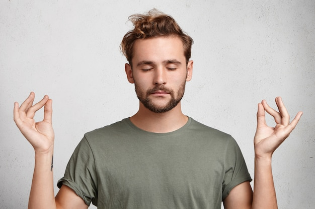 L'uomo barbuto concentrato dall'aspetto accattivante medita
