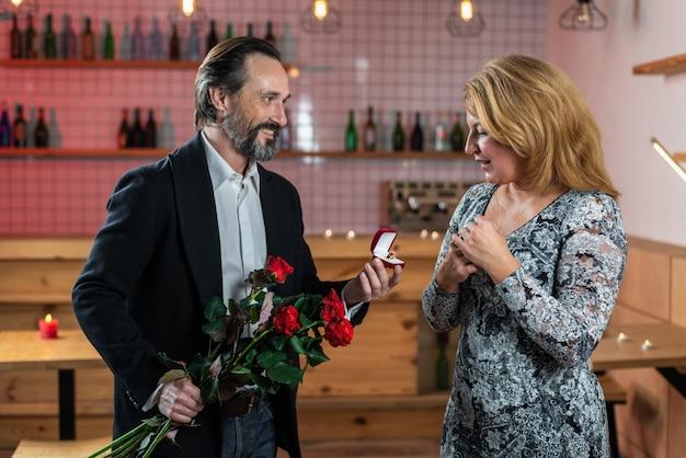 L'uomo barbuto fa una proposta di matrimonio a una donna con un mazzo di rose