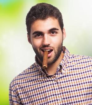 L'uomo barbuto fuma il sigaro.