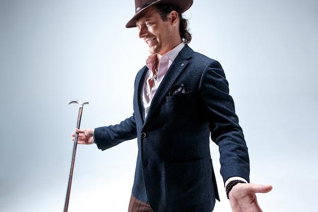 L'uomo barbuto maturo in un vestito e una canna della holding del cappello.