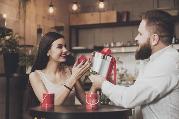 L'uomo barbuto regala un regalo alla bella ragazza