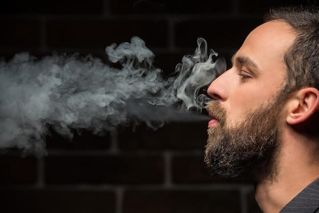 L'uomo barbuto sta fumando contro il muro di mattoni.