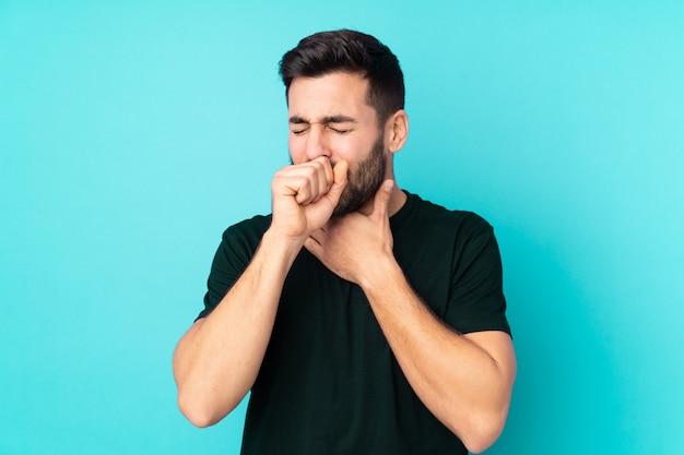 L'uomo bello caucasico isolato sulla parete blu sta soffrendo di tosse e si sente male