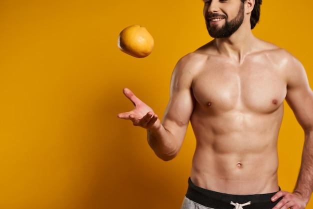 L'uomo bello con il torso nudo getta l'arancia.