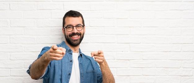 L'uomo bello con la barba sopra il muro di mattoni bianco indica il dito mentre sorride