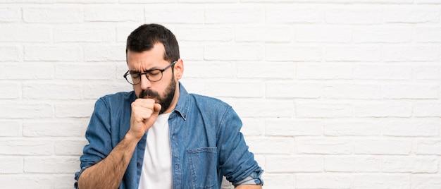 L'uomo bello con la barba sopra il muro di mattoni bianco soffre di tosse e si sente male