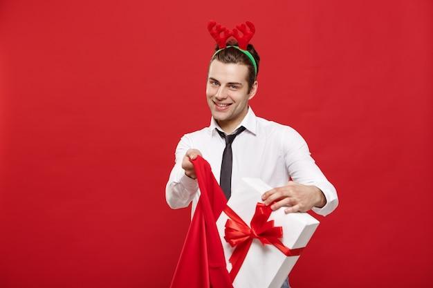 L'uomo bello di affari celebra il buon natale ed il buon anno indossano il cinturino della renna che tiene la grande borsa rossa di santa.