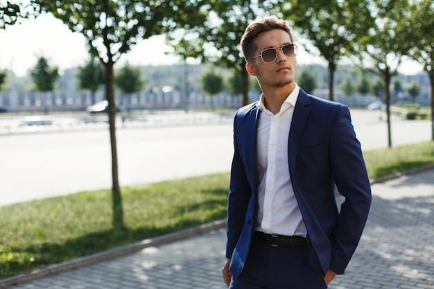 L'uomo bello in un vestito di affari cammina lungo la via in un giorno soleggiato