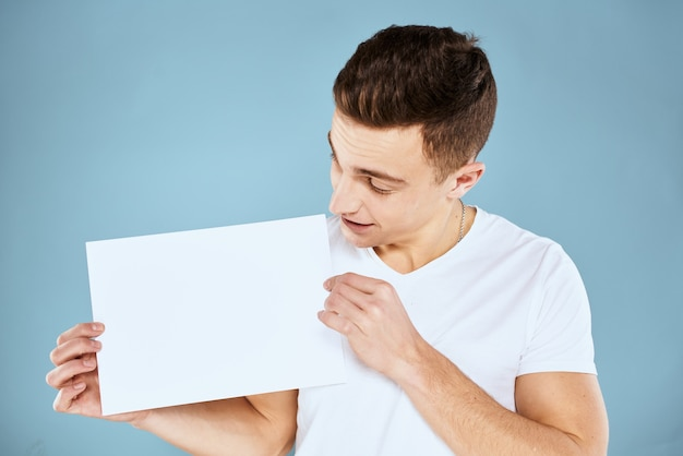L'uomo bello in una maglietta tiene un foglio bianco senza un'iscrizione, spazio libero, spazio vuoto, spazio della copia