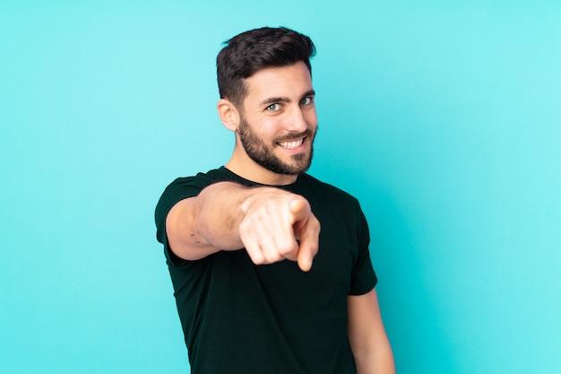 L'uomo bello isolato sulla parete blu indica il dito con un'espressione sicura