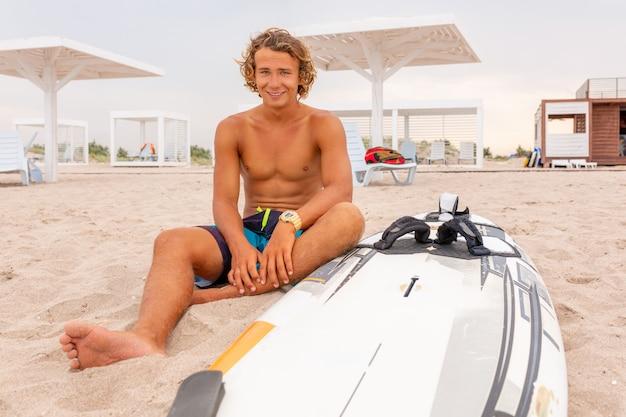 L'uomo bello si siede sulla spiaggia con la tavola da surf in bianco bianca aspetta l'onda per navigare il punto alla riva dell'oceano del mare. concetto di sport, fitness, libertà, felicità, nuova vita moderna, vita bassa.