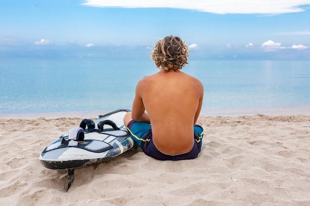 L'uomo bello si siede sulla spiaggia con la tavola da surf in bianco bianca aspetta l'onda per navigare il punto alla riva dell'oceano del mare.