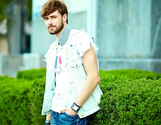 L'uomo bello sorridente divertente dei pantaloni a vita bassa in estate alla moda copre la posa sul fondo della via