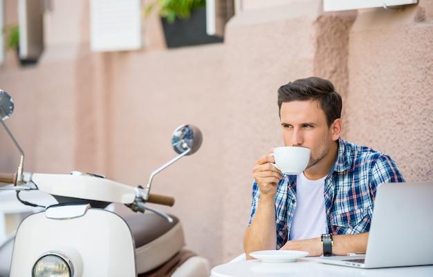 L'uomo bello sta rilassandosi in caffè e sta bevendo il caffè.
