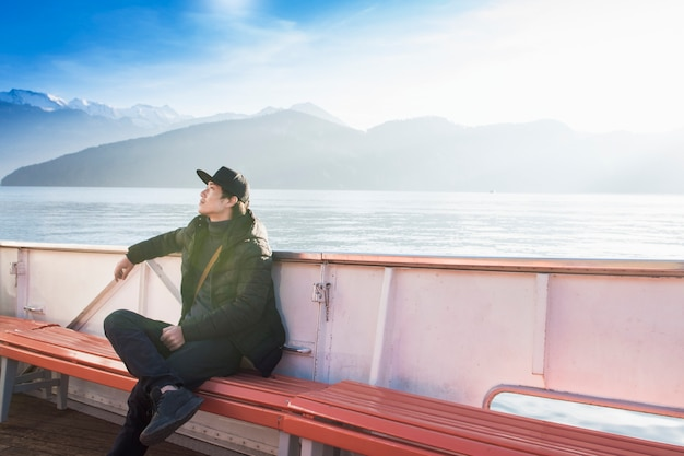 L'uomo bello sta sedendosi sulla barca con la montagna