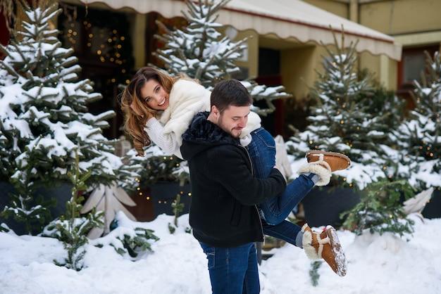 L'uomo bello tiene la sua bella amica sorridente sulla sua spalla dell'albero di natale con le luci. vacanze invernali, natale e capodanno.