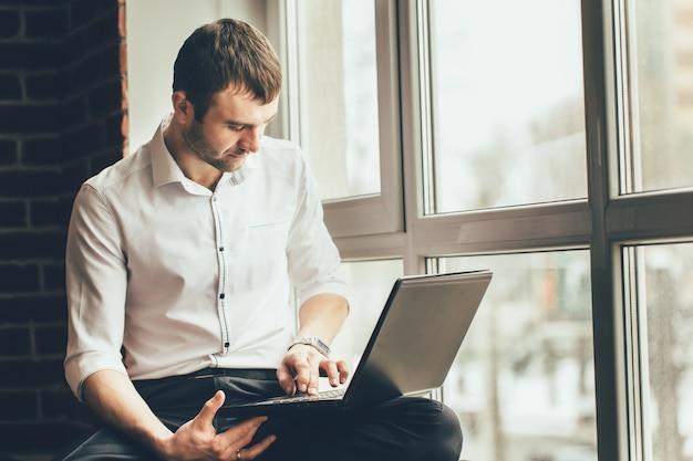 L'uomo bello tiene un computer portatile in sue mani vicino alla finestra. lavora su un compito importante a casa