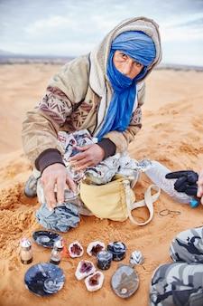 L'uomo berbero nel deserto del sahara offre souvenir e pietre preziose
