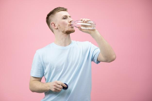 L'uomo beve acqua potabile pulita da una bottiglia dopo l'allenamento