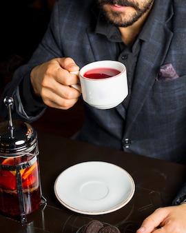L'uomo beve una tazza di tè alla frutta