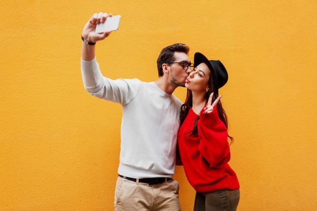L'uomo bianco bello con la barba e la donna castana allegra sveglia che fanno l'autoritratto e mostra i segni a mano.