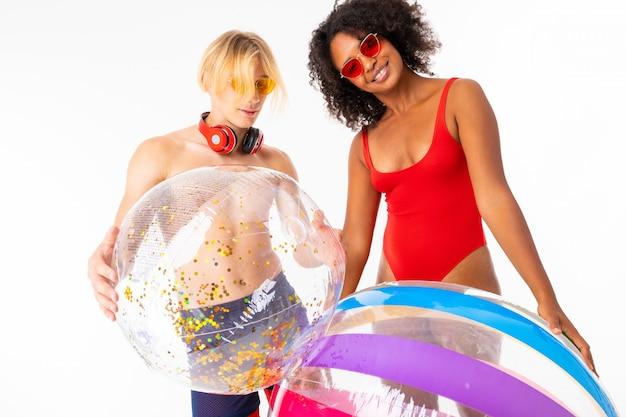 L'uomo biondo femminile e caucasico africano sta in costume da bagno con le grandi palle e sorrisi di gomma, isolati su fondo bianco