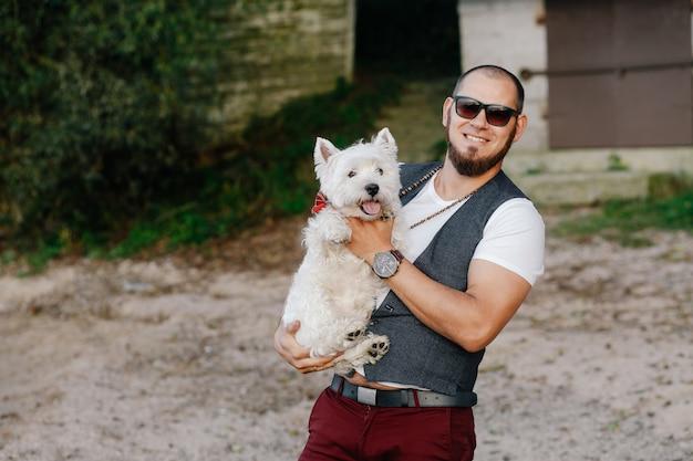L'uomo brutale abbraccia il suo cagnolino bianco