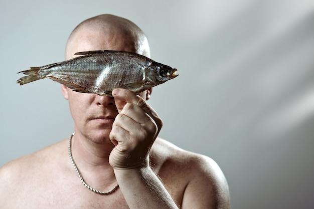 L'uomo brutale calvo con un torso nudo tiene un pesce essiccato davanti alla sua faccia
