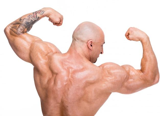 L'uomo calvo mostra i muscoli della schiena