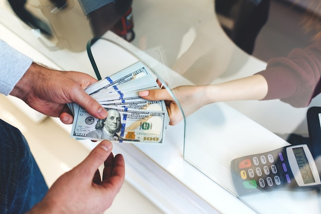 L'uomo cambia denaro in uno scambio di valuta, una grande somma di dollari, un aumento del tasso di cambio, da vicino un denaro che cambia le mani delle persone