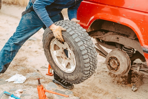 L'uomo cambia manualmente la ruota su un fuoristrada 4x4