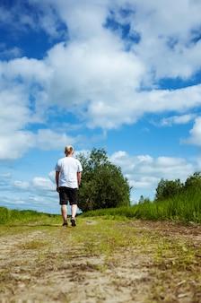 L'uomo cammina lungo un sentiero vicino a una foresta in pantaloncini scuri e una maglietta bianca.