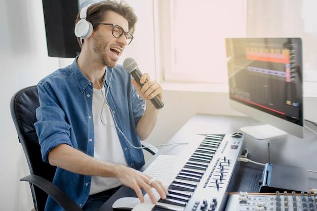 L'uomo canta nel microfono e lavora al mixer audio in studio di registrazione o dj in studio di trasmissione. il produttore musicale sta componendo una canzone sulla tastiera del sintetizzatore e sul computer in studio di registrazione.