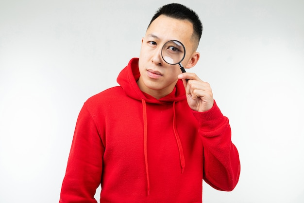 L'uomo castana in maglia con cappuccio rossa esamina la macchina fotografica attraverso una lente su un bianco