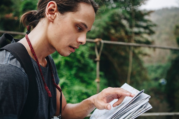 L'uomo caucasico che esamina una mappa viaggia ed esplora il concetto