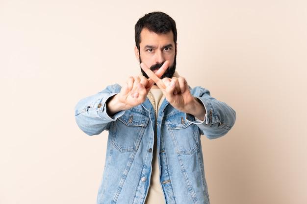 L'uomo caucasico con la barba sopra la fabbricazione isolata ferma il gesto con la sua mano per fermare un atto