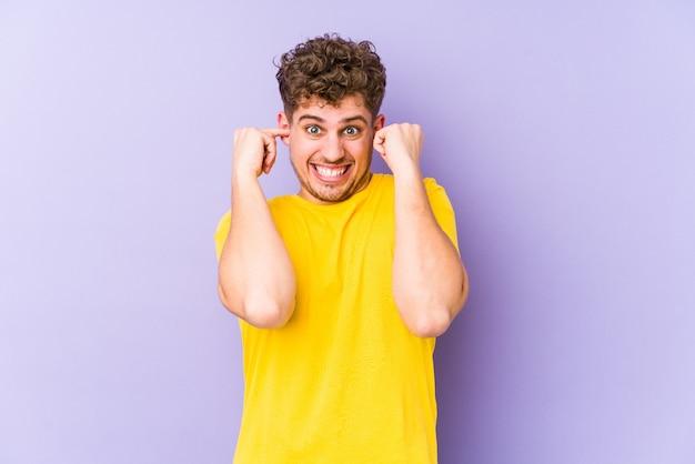 L'uomo caucasico dei giovani capelli ricci biondi ha isolato le orecchie di cono con le mani.