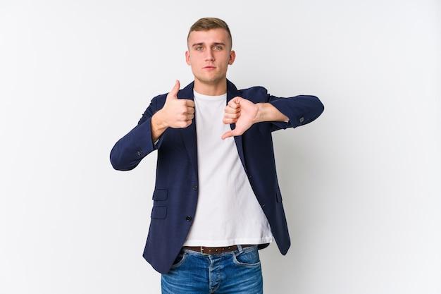L'uomo caucasico di giovani affari che mostra i pollici su e pollici giù, difficile sceglie il concetto