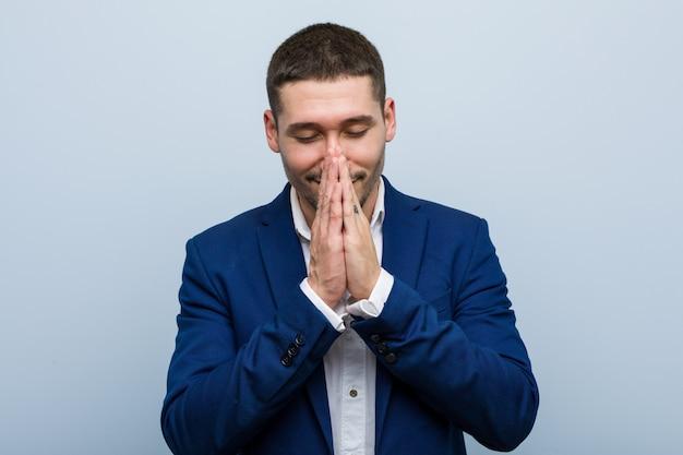 L'uomo caucasico di giovani affari che si tiene per mano dentro prega vicino alla bocca, si sente sicuro.