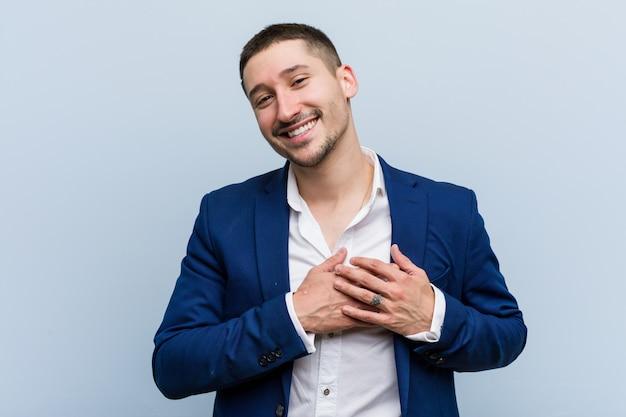 L'uomo caucasico di giovani affari ha espressione amichevole, premendo il palmo al petto. concetto di amore.