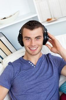 L'uomo caucasico di smiing ascolta musica con le cuffie