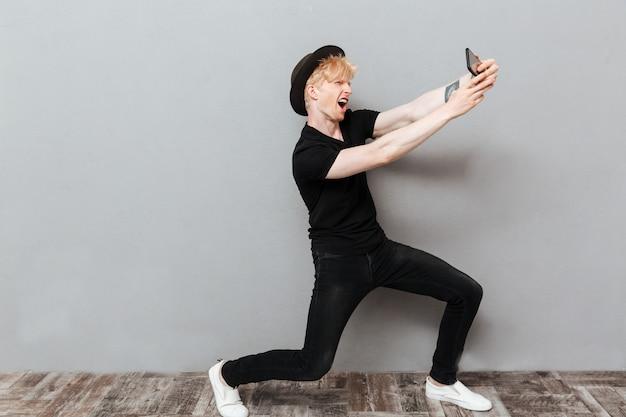 L'uomo caucasico divertente fa il selfie dal telefono cellulare.