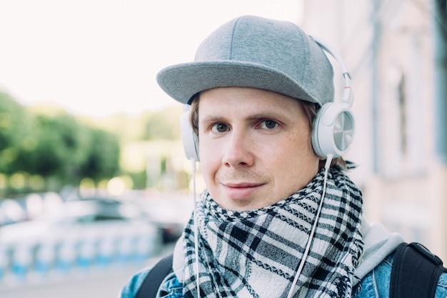L'uomo caucasico in un berretto per la strada ascolta musica