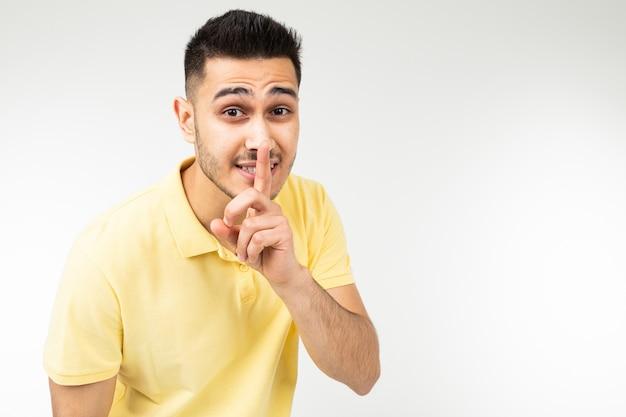 L'uomo caucasico in una maglietta gialla tiene un segreto su un bianco isolato