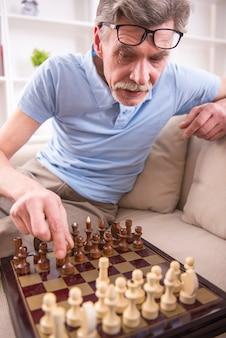L'uomo caucasico senior sta giocando a scacchi con un ragazzo.