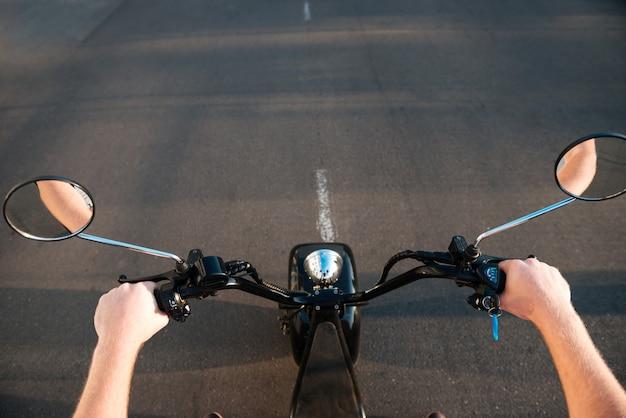 L'uomo cavalca su una moto moderna sulla strada all'aperto