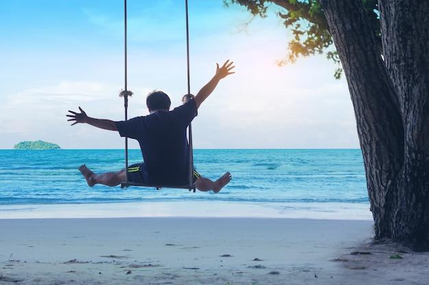 L'uomo celebra la libertà sull'altalena in spiaggia. viaggio di vacanze estive.
