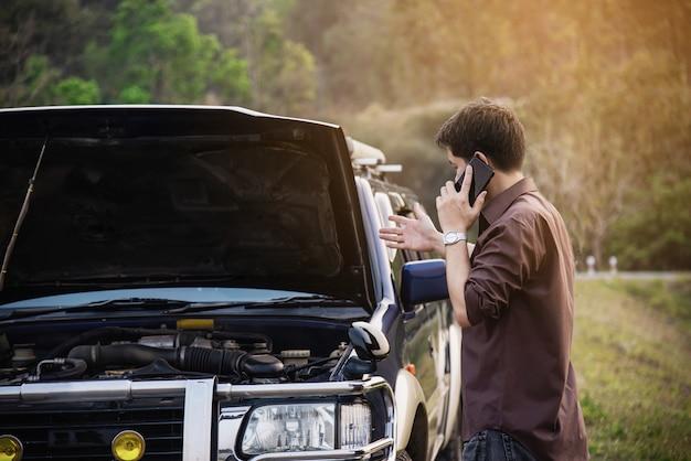 L'uomo cerca di risolvere un problema con il motore di un'auto in una strada locale